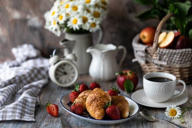 Croissants met verse rode aardbeien met een kopje koffie op een houten tafel en boeket van margrieten in een kruik. Premium Foto