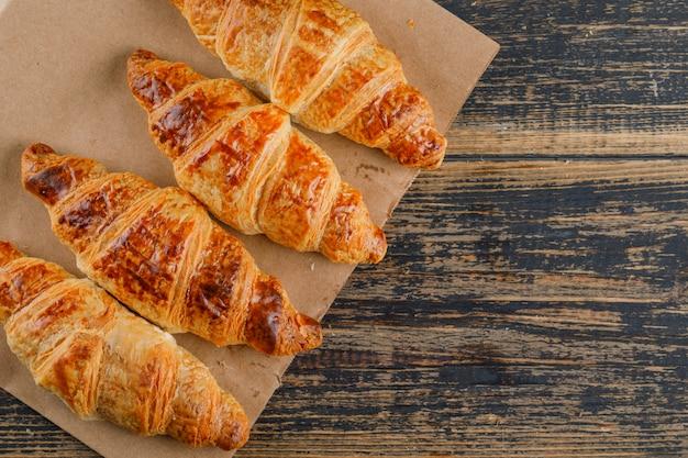 Croissants op houten en papieren zak. plat lag. Gratis Foto