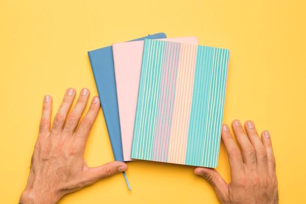 Crop handen met voorbeeldenboeken met creatieve covers Gratis Foto