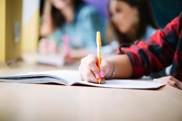 Crop student schrijven in notitieblok Gratis Foto