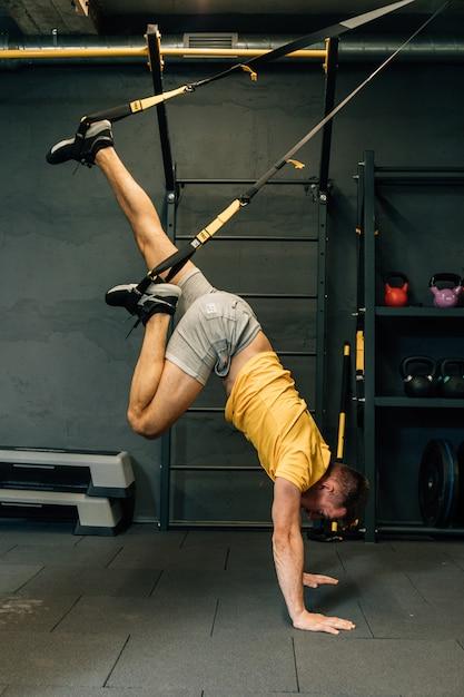 Crossfit fitness trx push ups man training bij sportschool. kracht en concentratie. jonge knappe man in sportkleding uitoefenen op sportschool. Premium Foto