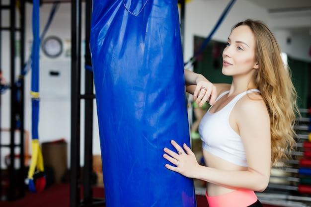Crossfit fitness vrouw boksen met blauwe bokszak op sportschool Gratis Foto
