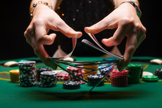 Croupier van het meisje schuifelt pokerkaarten in een casino Premium Foto