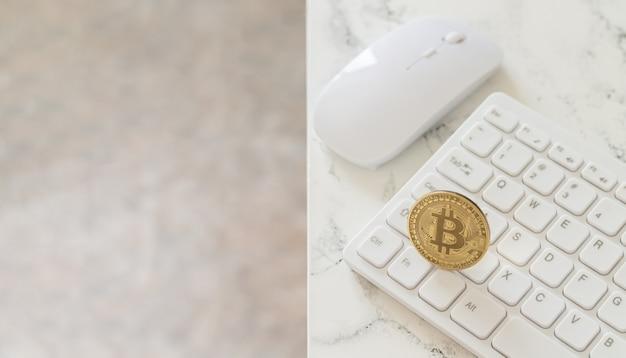 Cryptocurrency gouden bitcoin op wit computertoetsenbord naast muis op marmeren tafel Premium Foto