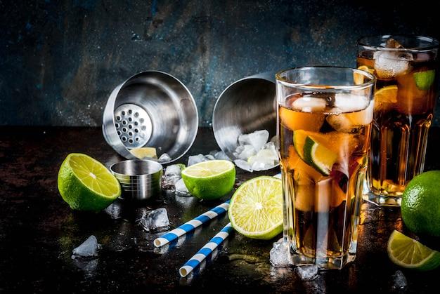 Cuba libre, long island of ijsthee cocktail met sterke alcohol, cola, limoen en ijs, twee glazen, donker Premium Foto