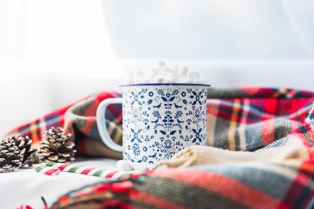 Cup met marshmallow in de buurt van sjaal en spar haken en ogen Gratis Foto