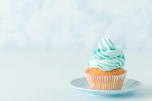 Cupcake met blauwe roomdecoratie op plaat - blauwe pastelkleur horizontale banner Premium Foto