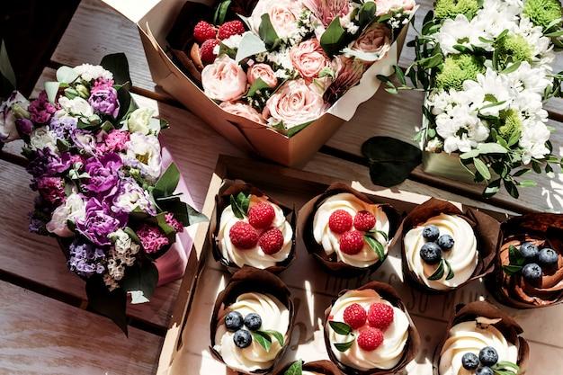 Cupcakes en bloemen in doos Premium Foto