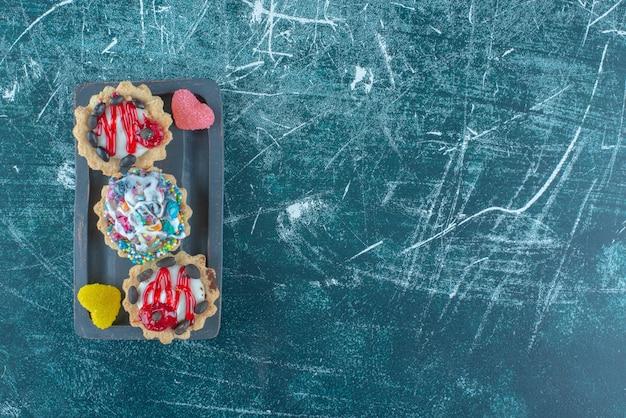Cupcakes en marmelades gebundeld op een schotel op blauwe achtergrond. hoge kwaliteit foto Gratis Foto
