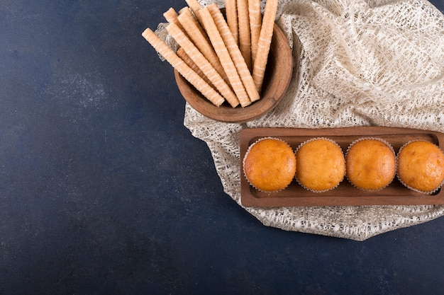 Cupcakes en wafelstokjes op een houten schaal in de bovenhoek Gratis Foto