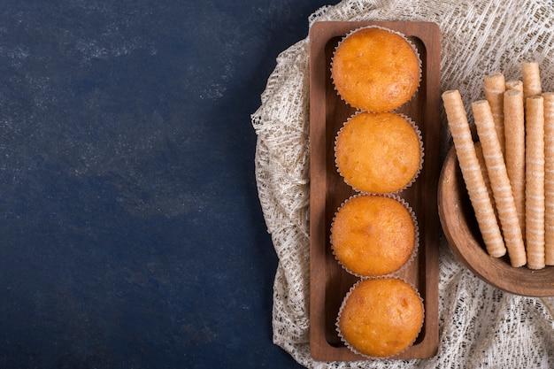 Cupcakes en wafelstokken op een houten schotel, bovenaanzicht Gratis Foto