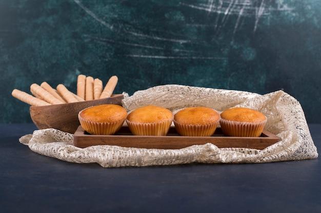 Cupcakes en wafelstokken op een houten schotel, hoekmening Gratis Foto