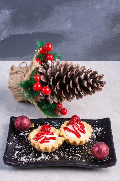 Cupcakes met aardbeiensaus op een zwarte schotel, gebundeld met kerstversieringen op marmeren oppervlak Gratis Foto