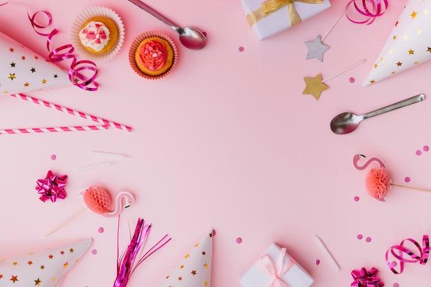 Cupcakes; wimpel; rietjes; prop; lepel; kaars; geschenkdozen; confetti en feestmuts op roze achtergrond Gratis Foto