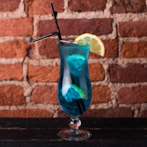 Curassao blauwe cocktail met citroen in een glazen bokaal Premium Foto