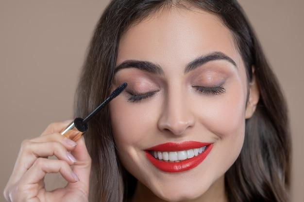 Dag make-up. gelukkig lachend mooie jonge vrouw met heldere lippen wimpers kleuren met zwarte mascara Premium Foto