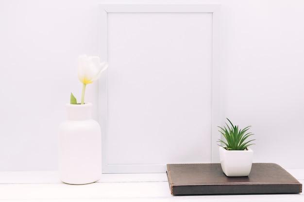 Dagboek; fabriek; tulp bloem met lege fotolijst op witte tafel Gratis Foto