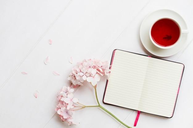Dagboek met kopje thee en bloemen Premium Foto