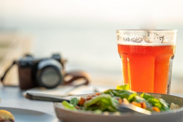 Dagboek met pen en salades geplaatst op de strandtafel. de vacante kant Premium Foto