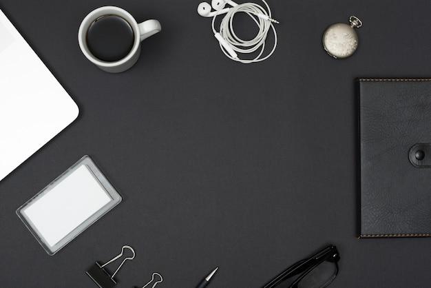 Dagboek; oortelefoon; koffiekop; laptop; paperclips; bril op zwarte desktop Gratis Foto