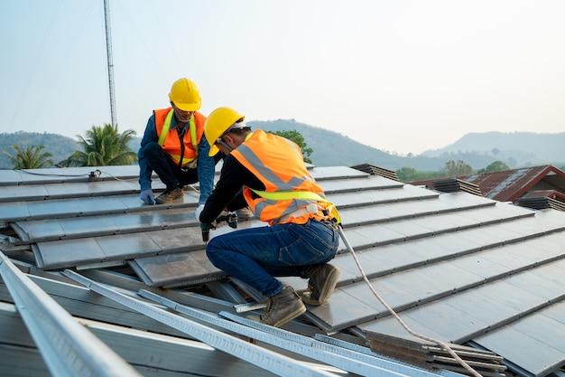 Dakdekker bouwer werknemer keramische dak installeren bovenop het nieuwe dak op bouwplaats. Premium Foto