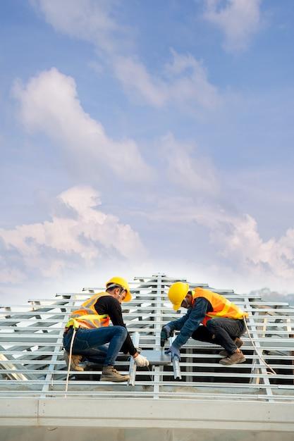 Dakdekker werknemer in beschermende uniforme slijtage en handschoenen, met behulp van lucht of pneumatisch schiethamer en het installeren van betonnen dakpan bovenop het nieuwe dak, concept van woningbouw in aanbouw. Premium Foto