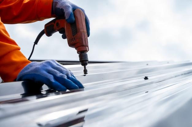Dakdekker werknemer met behulp van lucht of pneumatische schiethamer en het installeren van metalen plaat bovenop het nieuwe dak. Premium Foto
