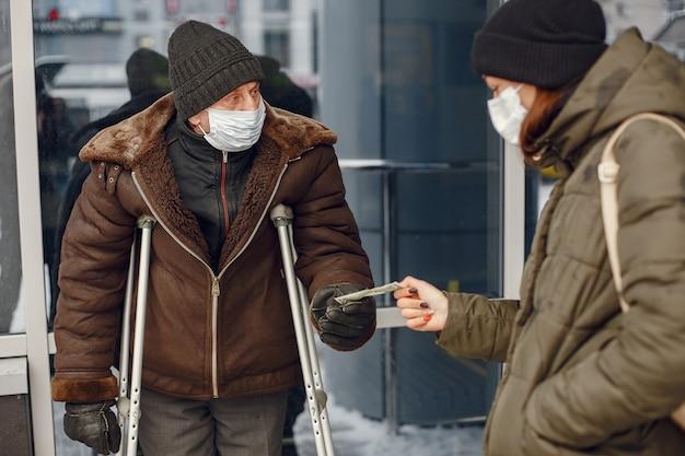 Dakloos in een winterstad. man die om voedsel vraagt. Gratis Foto
