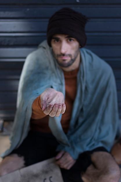 Dakloze man bedelen voor geld hoog zicht Gratis Foto