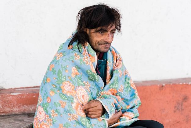 Dakloze man buiten onder deken Gratis Foto