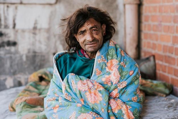 Dakloze man buitenshuis onder deken Gratis Foto