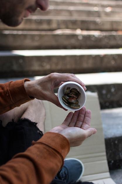 Dakloze man die zijn wisselgeld telt Gratis Foto