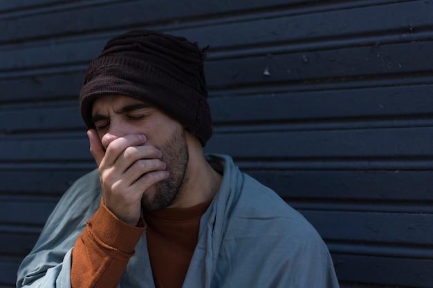 Dakloze man geeuwen en zijn mond bedekken Gratis Foto