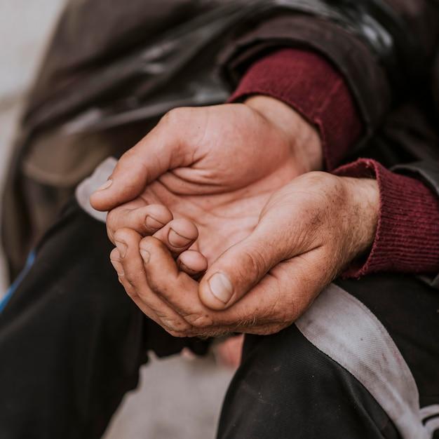 Dakloze man hand in hand om hulp Premium Foto