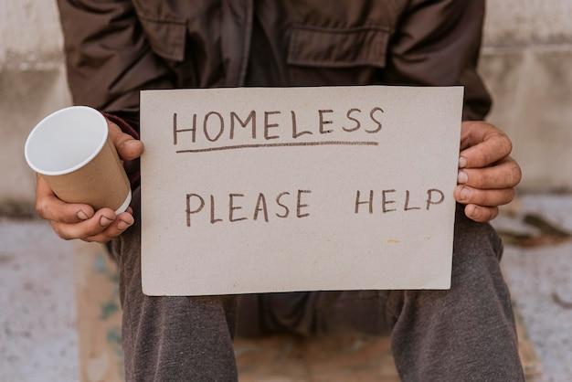 Dakloze man met beker en help ondertekenen Gratis Foto
