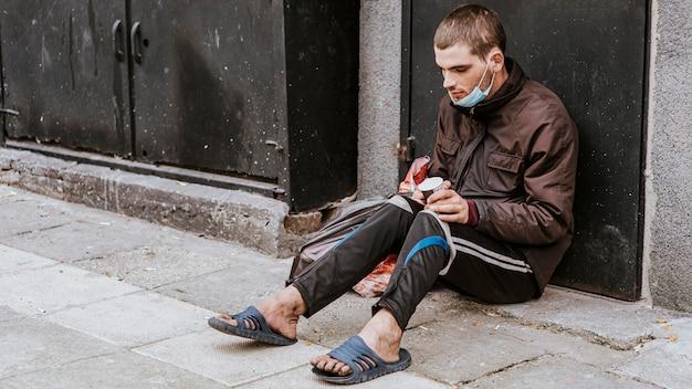Dakloze man met medisch masker en beker Premium Foto