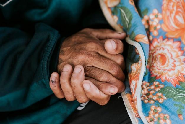 Dakloze man met zijn handen met deken Premium Foto
