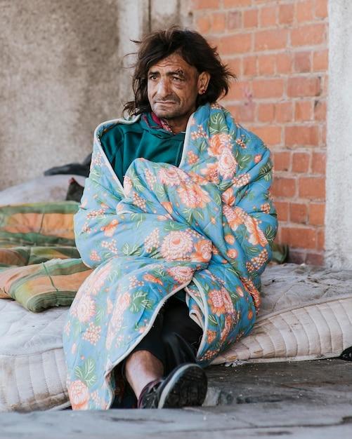 Dakloze man op matras buiten onder deken Gratis Foto