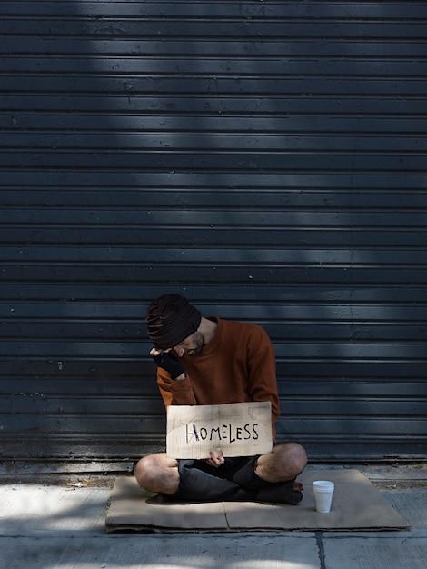 Dakloze man verbergt zijn gezicht en vraagt om geld Gratis Foto