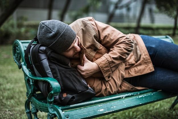 Dakloze mensen die op bank in het park slapen Premium Foto
