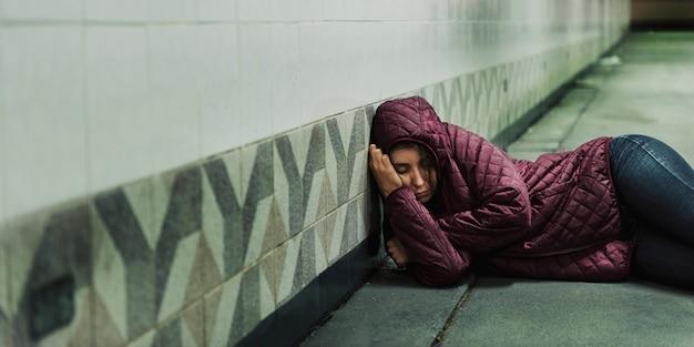 Dakloze vrouw slaapt op de vloer Premium Foto