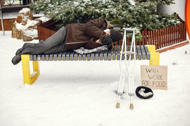 Daklozen liggend op een bankje. Gratis Foto