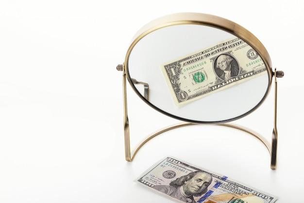 Dalende inkomens door pandemisch coronavirus covid-19. 100 dollar wordt in de spiegel weergegeven als één dollar. concept van een wereldwijde crisis. Premium Foto