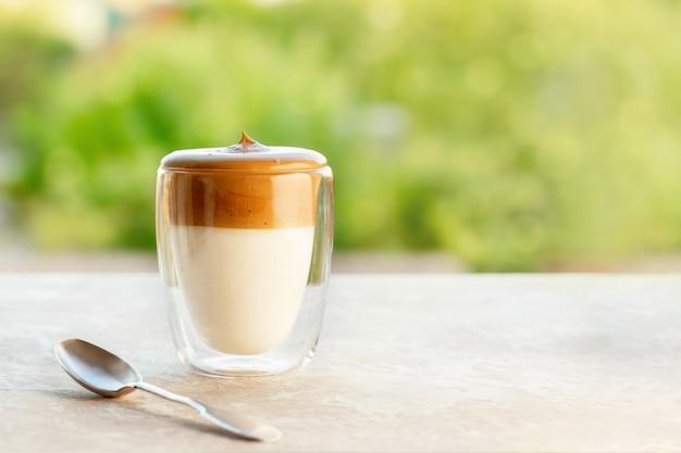 Dalgona schuimende koffie in glas met lepel op lijst aangaande groene achtergrond. trend koreaanse iced latte koffiedrank met schuim van instant koffie met kopie ruimte voor tekst. Premium Foto