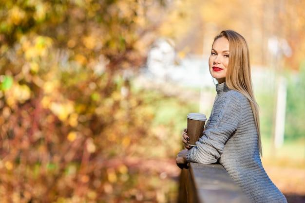 Dalingsconcept - mooie vrouw het drinken koffie in de herfstpark onder dalingsgebladerte Premium Foto
