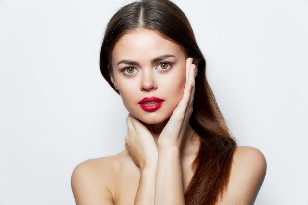 Dame blote schouders schone huid rode lippen handen in de buurt van gezicht aantrekkelijke look geïsoleerde achtergrond Premium Foto