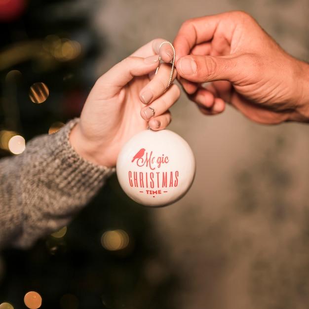 Dame die aan de kerstbal van kerel decoratieve geeft Gratis Foto
