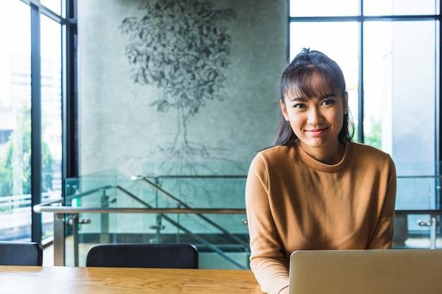 Dame die bij laptop aan tafel werkt Gratis Foto