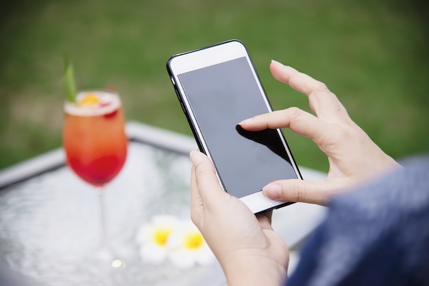 Dame die mobiele telefoon met behulp van ontspant in groene tuin Gratis Foto