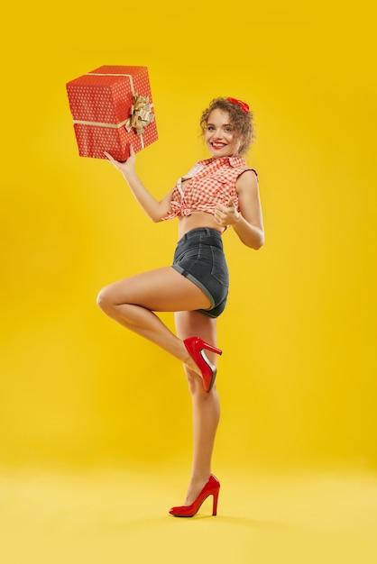 Dame die zich op één been bevindt dat rode doos met gouden boog houdt. Premium Foto